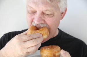 man biting into fresh doughnut